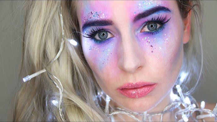 frisur mit langem blonden haar und kleinen weißen leuchten, eine frau mit einhorn schminken mit glitzer und violettem lidschatten und einem schwarzen lidstrich