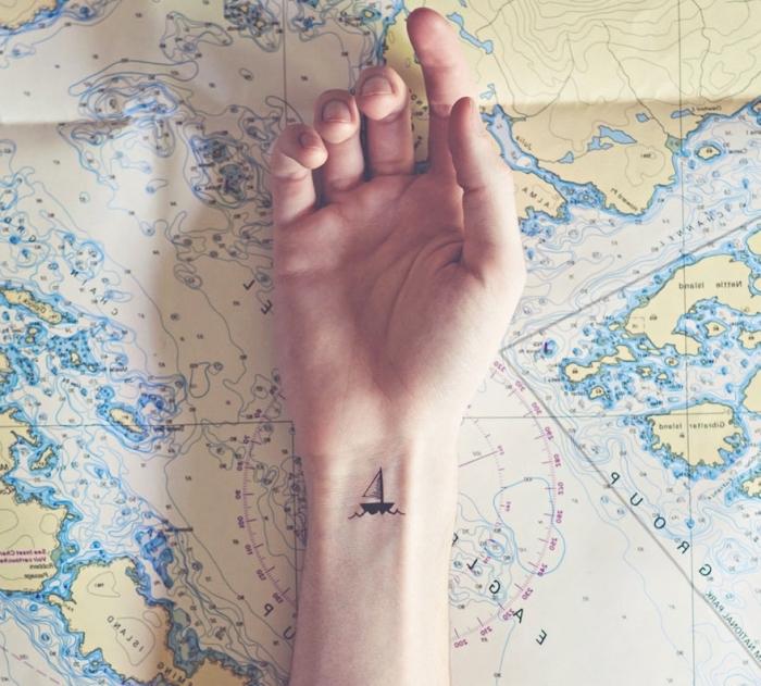 tattoo arm frau, boor, schiff, arm liegt auf einer karte, weltreise nternehmen, tattoo zur inspo