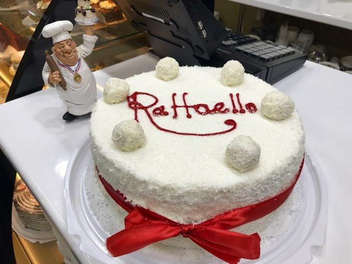 Raffaello Torte mit Kokos Raspeln, eine rote Aufschrift und rote Schleife, Raffaello selber machen