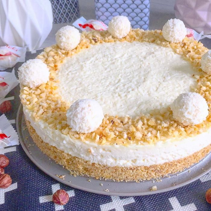 Kokos Torte mit Nüssen umrandet, orange und weiße Torte mit Raffaello Pralinen