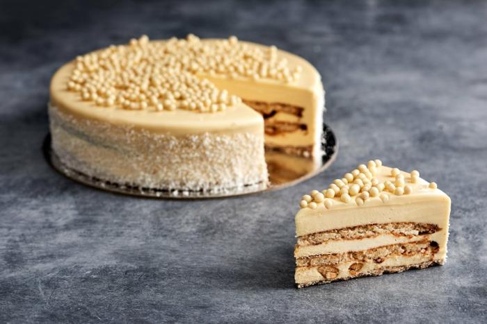 orange Creme von Kokos Torte, runde weiße Schokoladenstreusel, Kekse Boden