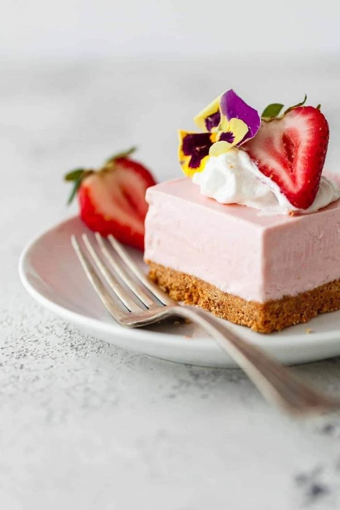 torte mit erdbeeren, philadelphia käsekuchen dekoriert mit früchte, sahne und kleine blüten