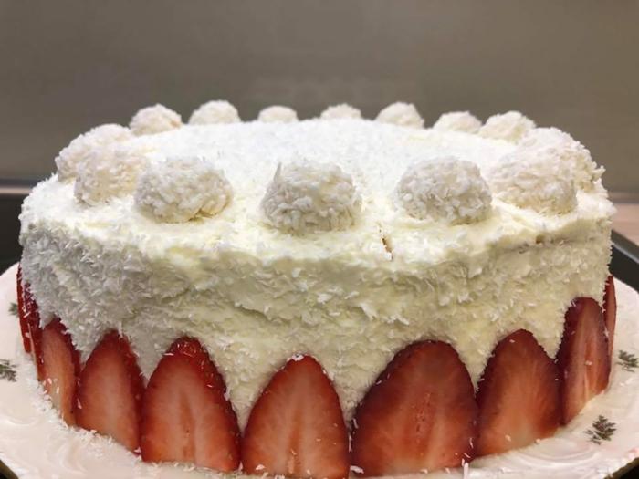 Raffaello Erdbeertorte, geschnittene Erdbeere umranden die Torte mit Kokosraspeln