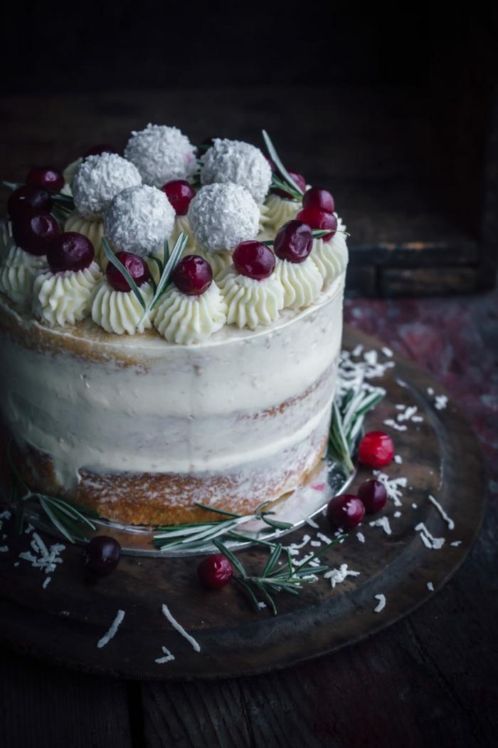 eine Torte mit weißer Creme bedeckt, gelbe Blütten mit Kirschen als Dekoration