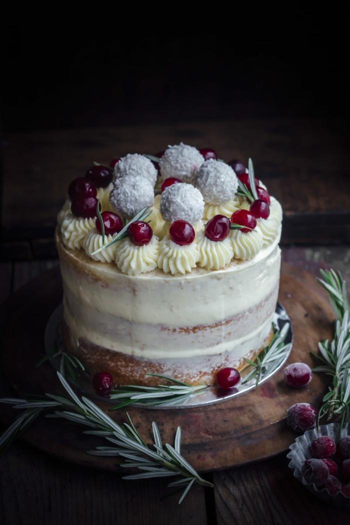 eine weiße Torte mit gelben und roten Akzente, Raffaello Torte, grüne Blätter,