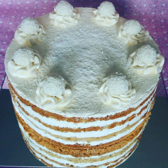 weiße Creme von der Torte, weiße Blumen und weiße Raffaello Pralinen, Kokos Torte