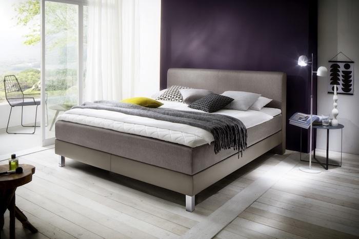 ein schlafzimmer mit violetter wand und einem boxspringbett