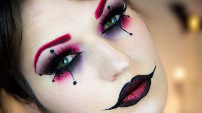 clown frauenmakeup halloween schminkideen, dunkle lippen und augen make up, lila augenbrauen, weißes gesicht