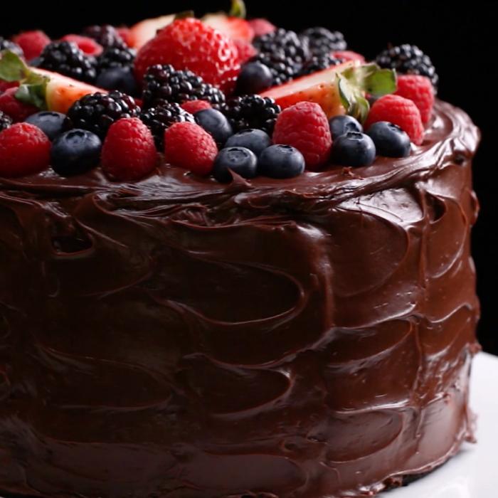 schokokuchen saftig, torte mit schokoladen ganache garniert mit erdbeeren, blaubeeren, brombeeren und erdbeeren