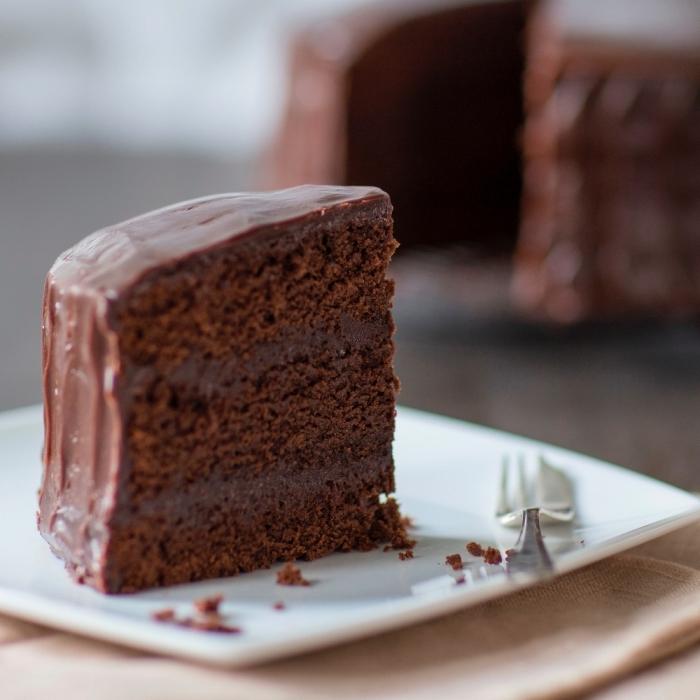 schokoladenkuchen saftig, stück torte mit schokoalde, eckiger weißer teller, gabel