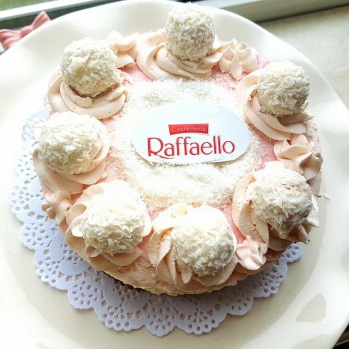 eine rosa Torte, Kokosraspeln in der Mitte, das Zeichen von Raffaello, Kokos Torte
