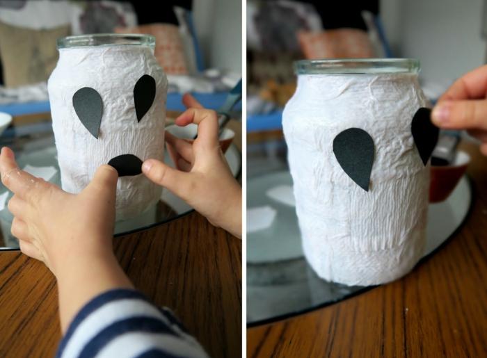 ein gruseliges Gespenst mit Augen und Mund von Hände des Kindes befestigt, Laterne für Kinder
