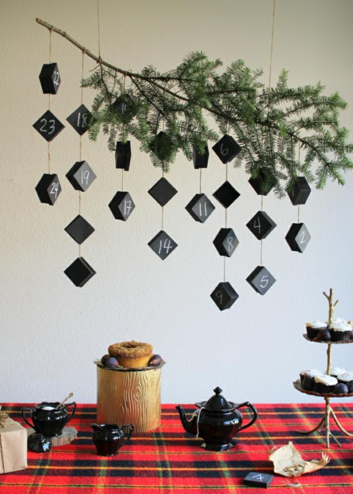 ein Zweig mit kleinen schwarzen Schachteln, die davon hängen, ein Tisch zur Teeparty gedeckt
