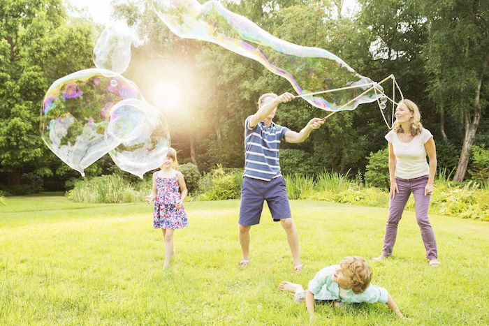 erwachsene und kleine kinder und große seifenblasen