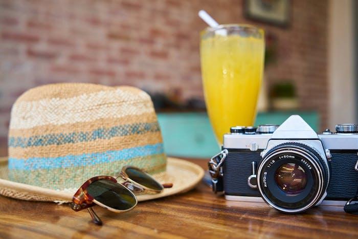 Was gehört ins Reisegepäck, Sommerhut Sonnenbrille und Kamera