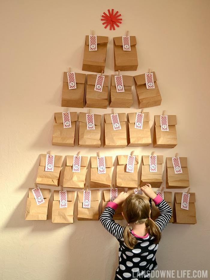 ein Mädchen hängt Tüte von dem Adventskalender, braune Tüten mit gestreiften Anhänger, DIY Adventskalender