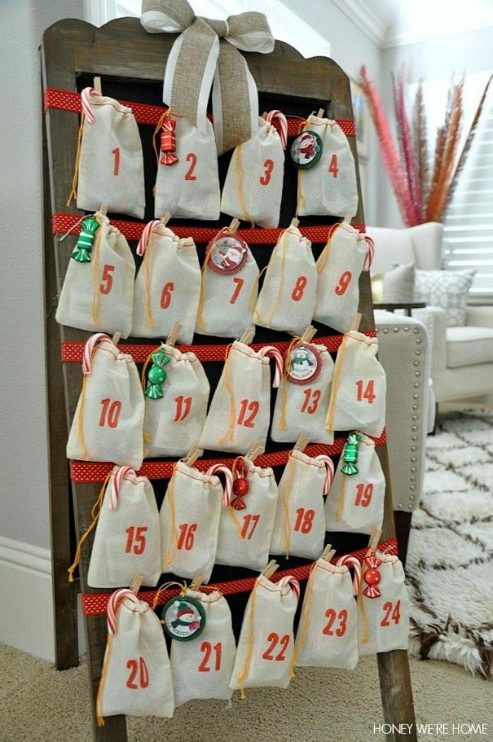 ein Rahmen aus Holz mit weißen Tüten geschmückt, auf denen rote Zahlen stehen, DIY Adventskalender