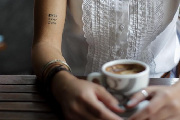 tattoo bilder, kaffee in den händen halten, armbänder, aufschrift in schwarz am hand