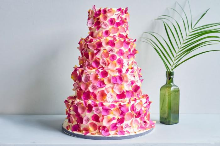 tortendeko hochzeit, große torte dekoriert mit rose blumenblättern, grüne glasflasche