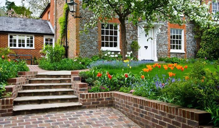 ein haus mit weißen fenstern und ein kleiner vorgarten mit orangen und gelben blumen und grünen blättern, braune treppe im vorgarten