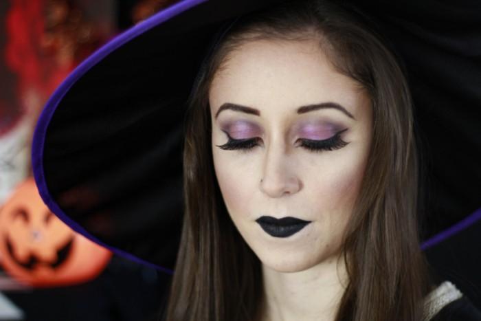 eine schöne hexe, lila make up und ein großer hut auf dem kopf, halloween gesicht schminken
