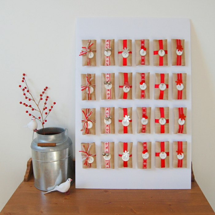DIY Adventskalender aus einen Menge Klopapierrollen mit roten Schleifen und runde Anhänger