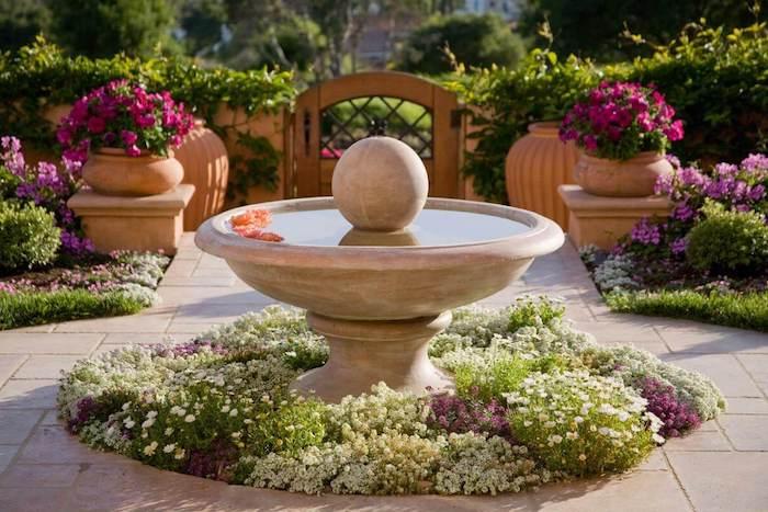 brunnen und ein kleiner vorgarten mit vielen kleinen weißen und violetten blumen, blumentöpfe it violetten blumen und ein zaun aus holz