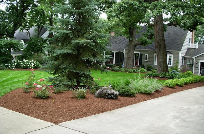 graues haus mit weißen fenstern und ein garten mit grünem rasen und bäumen und violetten blumen und kleinen vorgarten steinen