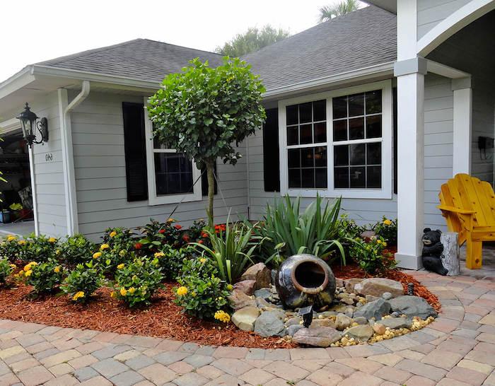 baum vorgarten, kleines graues haus aus holz mit weißen fenstern und ein kleiner vorgarten mit gelben blumen und grünen pflanzen und ein stuhl aus holz