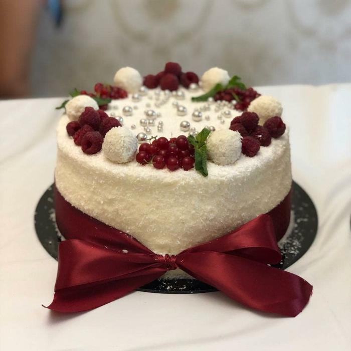 eine Mini Torte, die als echter Kunstobjekt aussieht, Raffaello Kuchen mit roter Schleife