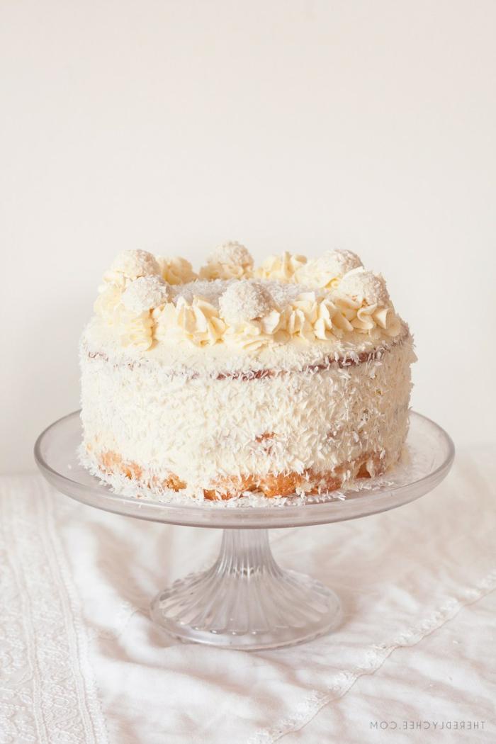 eine schöne Torte mit Kokosraspeln, gelbe Creme für die Blüten, sechs Raffaello Pralinen
