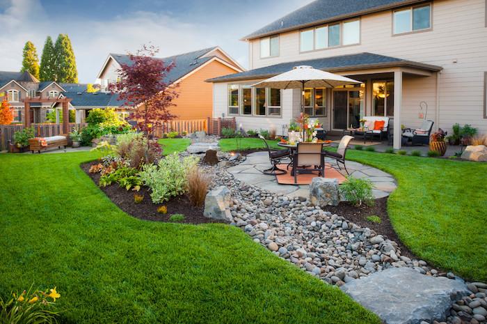 grüner rasen im großen vorgarten mit weißem sonnenschirm und stühlen und ein gartenweg mit vielen grauen steinen, ein vorgarten baum mit roten blättern