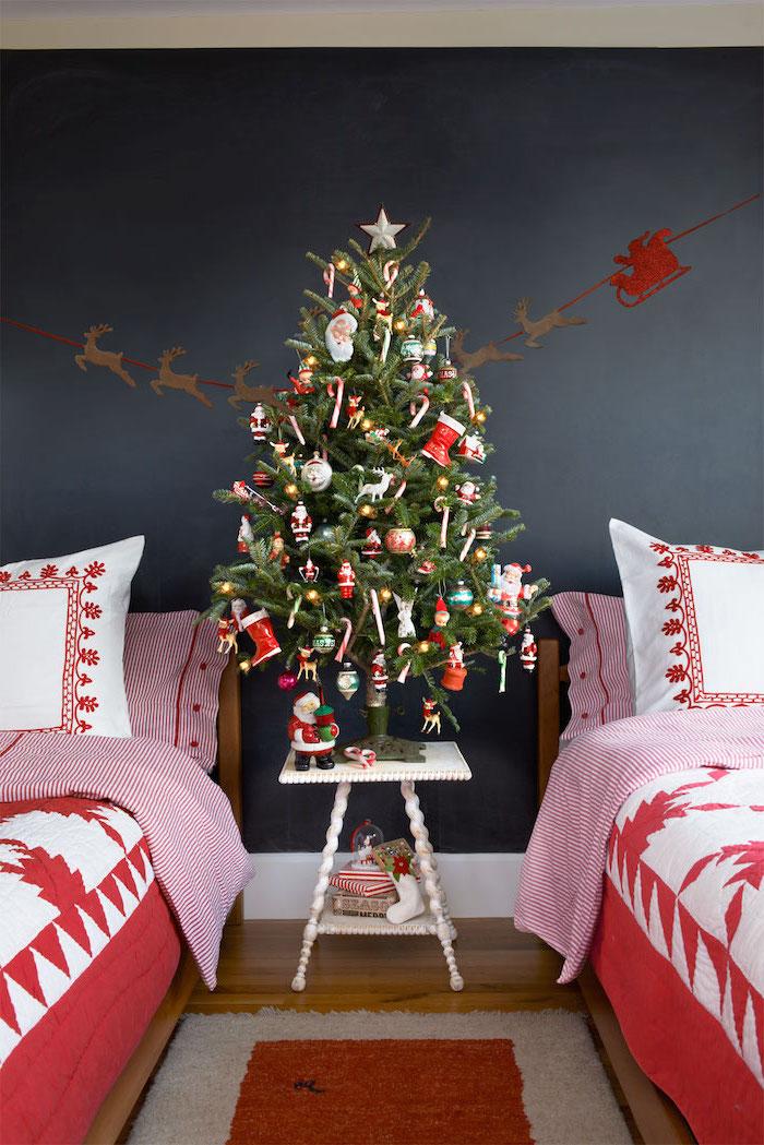 Wunderschöner Weihnachtsbaum mit vielen Christbaumkugeln zwischen zwei Betten im Kinderzimmer