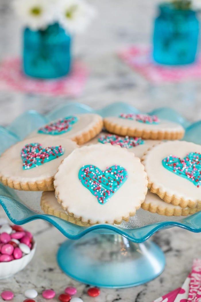 Schüssel voll mit leckeren Plätzchen, dekoriert mit weißer Schokolade, blauer Glasur und bunten Zuckerperlen