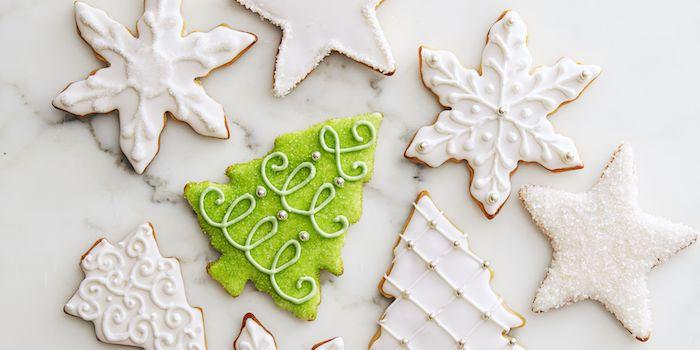 Plätzchen in Form von Christbäumchen und Schneeflocken mit Glasur und Zuckerperlen verzieren