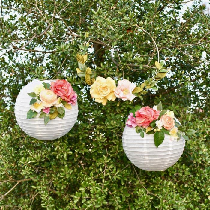 zwei weiße Laternen mit bunten Blumen verziert, auf einem grünen Baum gehängt, Lampion basteln