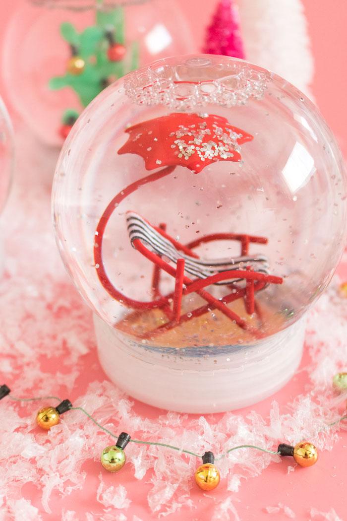 Tropische Schneekugel, Figur aus Plastik darin, Liegestuhl mit Sonnenschirm, silberner Glitter