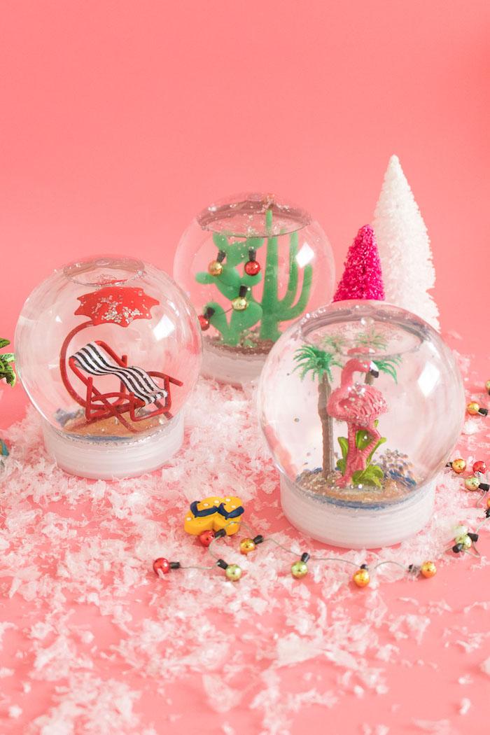 Drei tropische Schneekugeln mit sommerlichen Plastikfiguren, rosa Flamingo, Liegestuhl und Kakteen