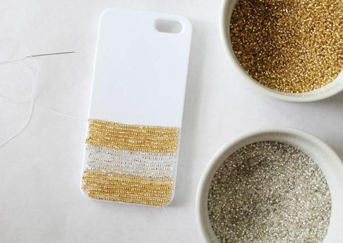 DIY Anleitung für Handyhülle erstellen, aufgeklebte Glasperlen in Gold und Weiß, kleine Nadel und weißer Faden