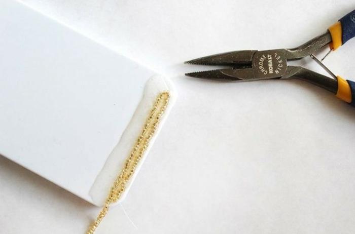 Handyhülle in weiß selber gestalten mit goldenen Glasperlen, aufgeklebt mit viel Klebstoff,