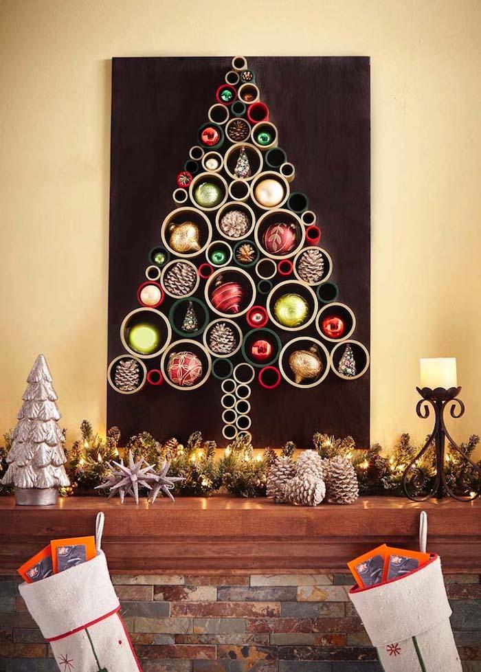 Weihnachtsbaum aus Papierrollen an der Wand, bunte Weihnachtskugeln darin, Tannengirlande auf dem Kamin, Zapfen und Duftkerzen