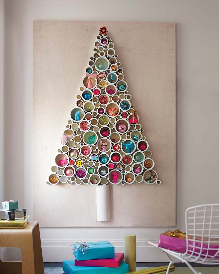 Weihnachtsbaum aus Papierrollen an der Wand, bunte Weihnachtskugeln darin , Weihnachtsgeschenke am Boden