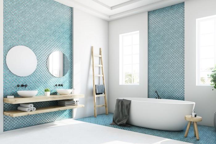 weiße kleine freistehende badewanne in einem blauen badezimmer mit blauen badezimmer fliesen und spiegeln und einem weißen waschbecken, badezimmer modern gestalten