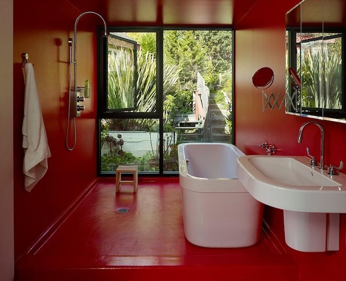roter boden und eine weiße badewanne und weißes waschbecken, badezimmer modern, badezimmer mit fenster