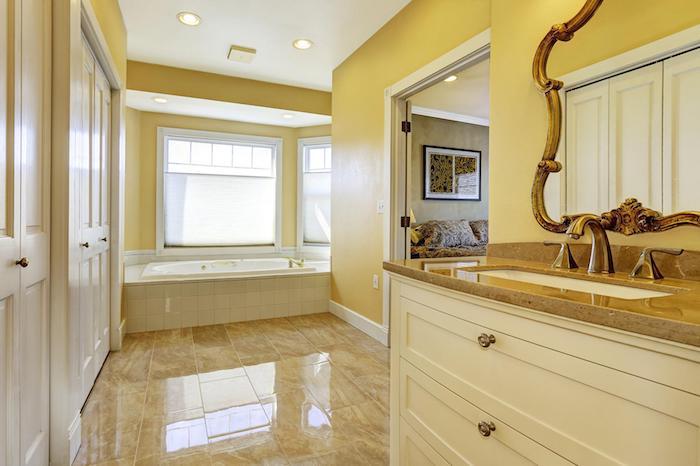 großes badezimmer mit gelben wänden und einem spiegel und fenstern. weiße freistehende badewanne