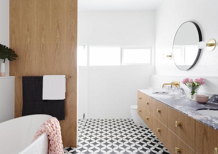 kleine weiße freistehende badewanne, ein badezimmer mit spiegel und fenstern, vase mit kleinen pinken blumen