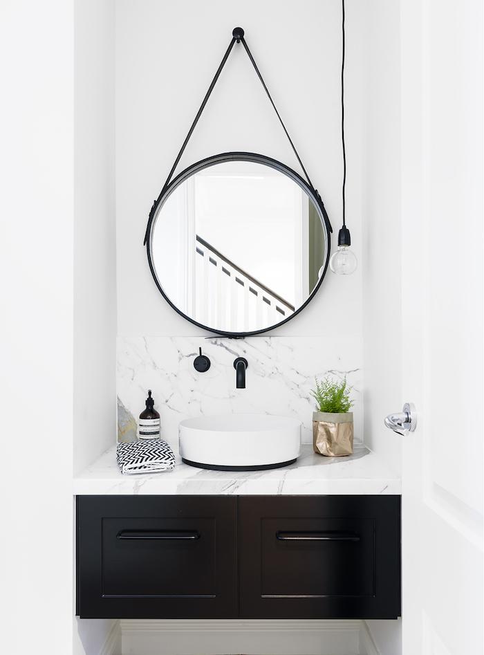 weißes waschbecken und ein spiegel, vase mit grünen pflanzen, badezimmer spiegelschrank