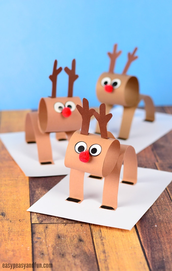 basteln weihnachten kinder, 3d hirsche aus papier, weiße blätter, tisch aus holz, rote nasen