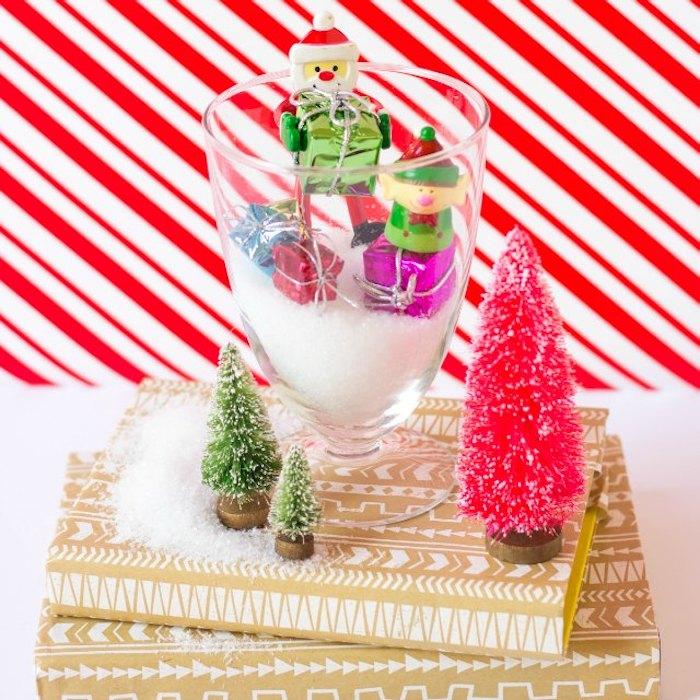 Künstlicher Schnee und kleine Weihnachtsfiguren in Glas füllen, bunte Weihnachtsbäume