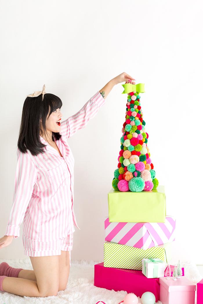 Weihnachtsbaum aus bunten Pompons auf Weihnachtsgeschenken, grüne Schleife an der Spitze